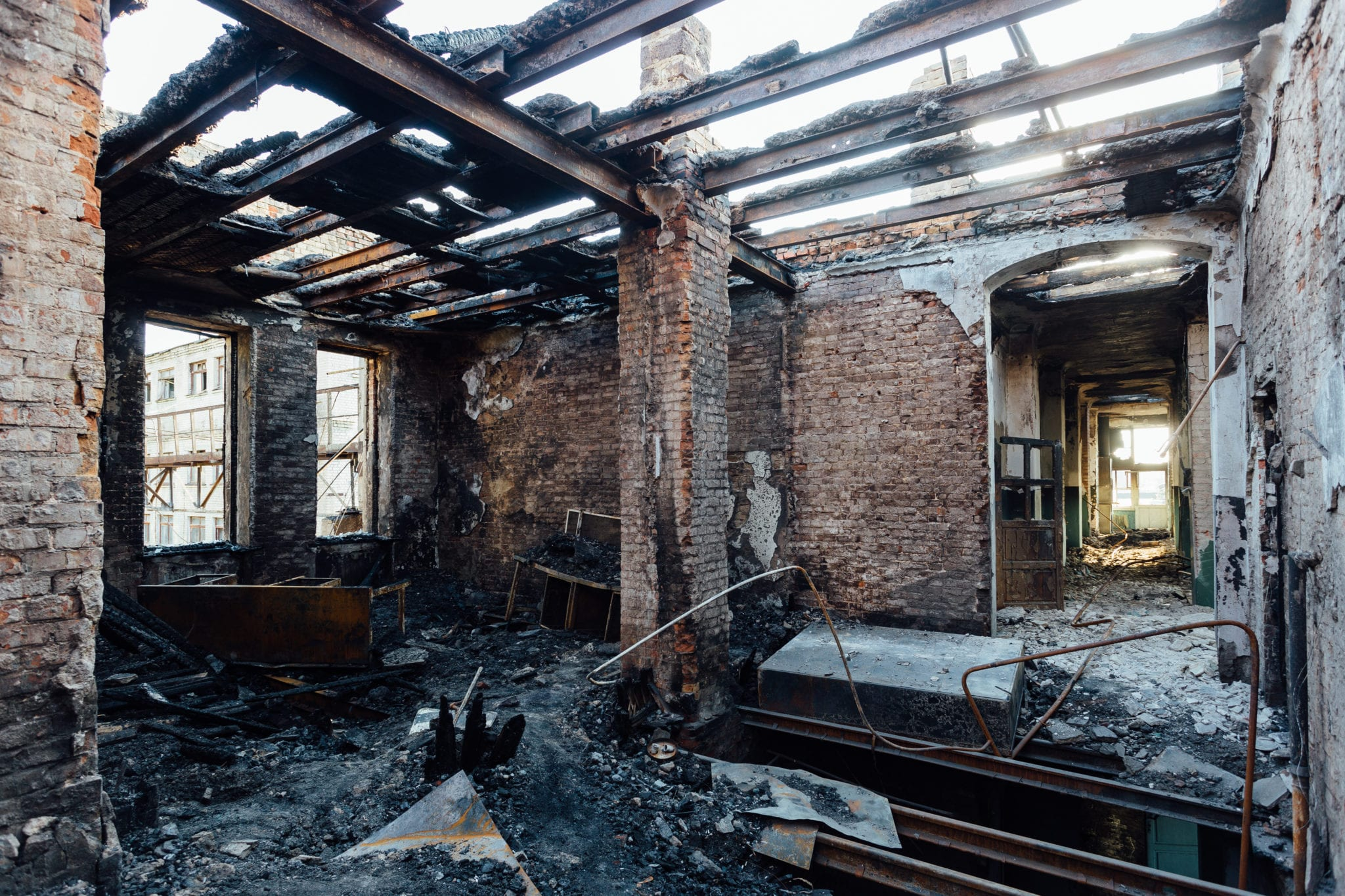 Burned interiors after fire in industrial or office building. Burnt furniture, failed roof